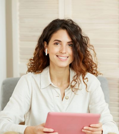 Attractive Caucasian woman with curly hair wearing white shirt holding pink tablet computer looking at camera smiling